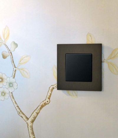 GIRA Esprit Dark Bronze light switch on patterned wall