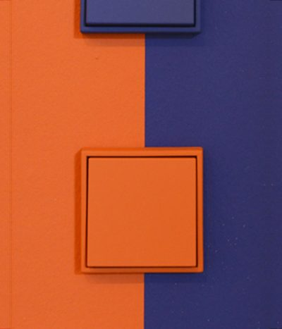 Jung Les COuleurs light switch in orange on blue wall
